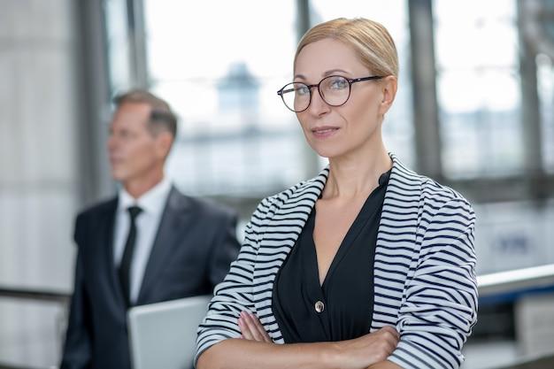 Tudo perfeitamente. mulher de negócios calma e confiante com óculos de mãos postas, olhando para a câmera e o homem em um terno formal com laptop atrás no aeroporto