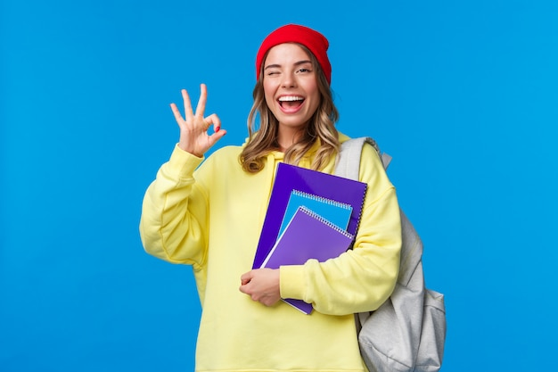 Tudo seja bom. a garota loira bonita e otimista pisca em aprovação e mostra um gesto correto, garante tudo perfeito, assegurada de que ela passará no teste, participará de aulas ou aulas na universidade
