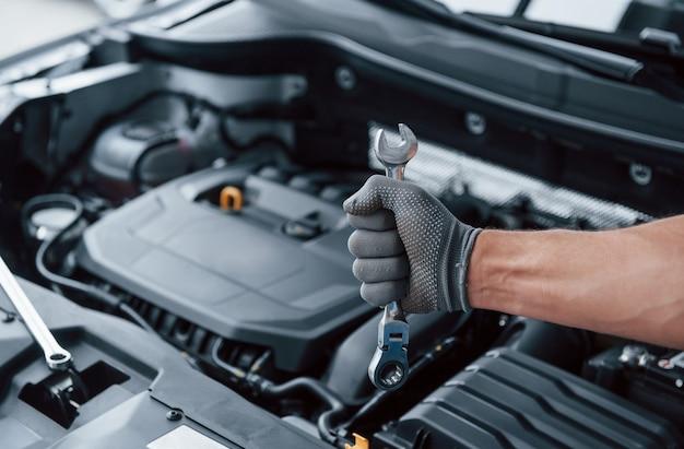 Tudo será consertado. a mão na luva segura a chave inglesa na frente de um automóvel quebrado