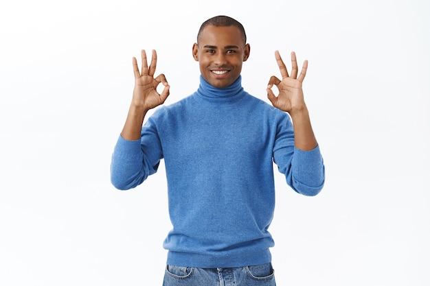 Tudo sobre controle. retrato de homem afro-americano satisfeito e confiante sorrindo, garantindo tudo de bom, mostrar gesto de aprovação concordando com a cabeça