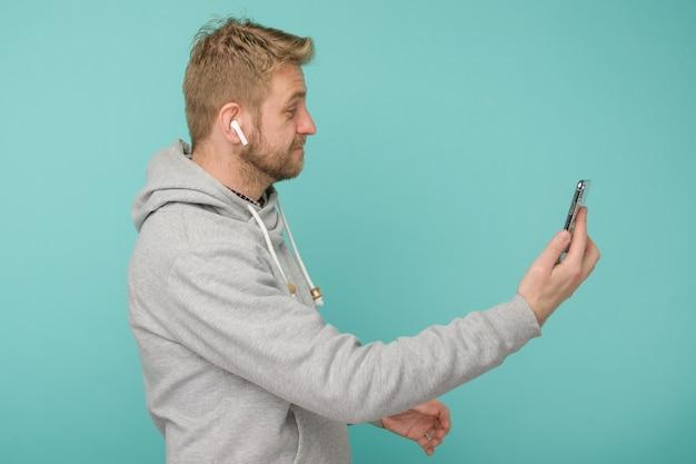 Tula, rússia - 1º de maio de 2019: homem feliz ouvindo música apple airpods sem fio - imagem