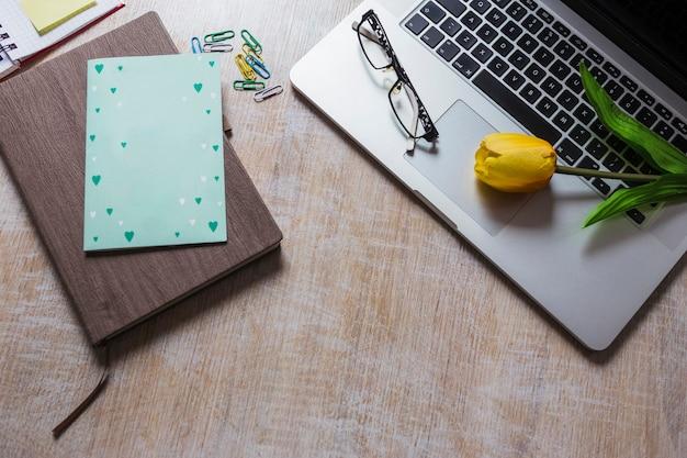 Tulipa e óculos no laptop com clipe de papel e diário na mesa