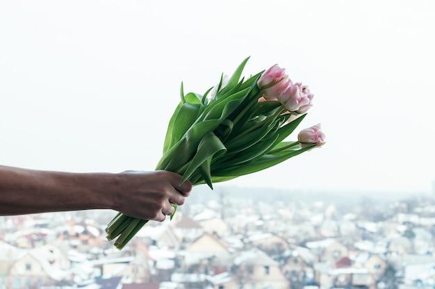 Tulipa flores na mão do homem contra urbano turva