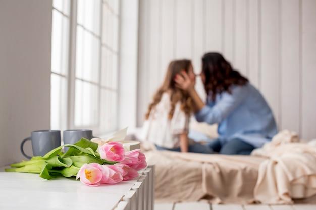 Tulipa flores na mesa perto da cama com abraçar mãe e filha