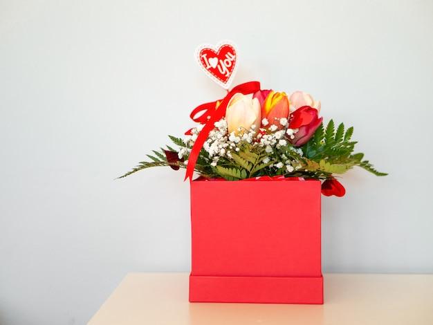 Tulipa na caixa de presente no fundo branco. flores da primavera. tulipas multicoloridas em uma caixa vermelha.