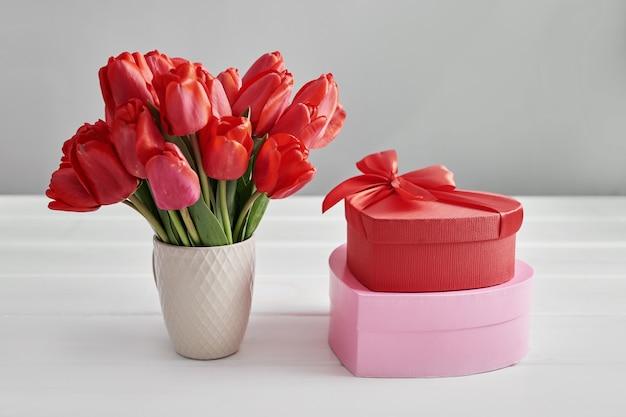 Tulipa vermelha flor e caixa de presente, isolada na mesa branca.