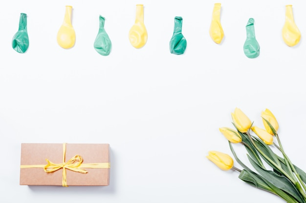 Tulipas amarelas, caixa de presente com laço e balões na superfície branca
