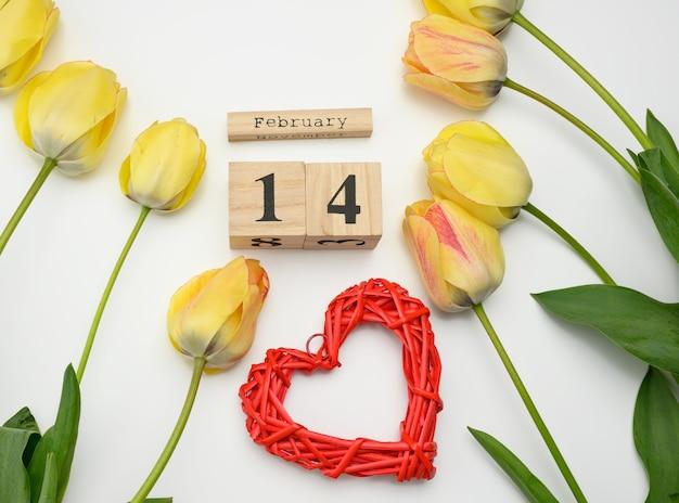 Tulipas amarelas, calendário de madeira com data de 14 de fevereiro e coração vermelho na superfície branca, vista superior