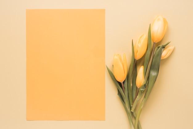 Tulipas amarelas com papel em branco na mesa
