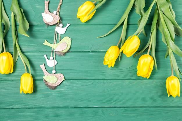 Tulipas amarelas com pequenos pássaros na mesa