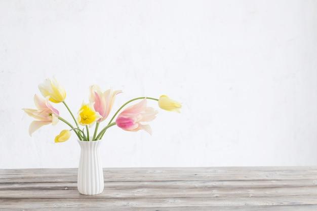 Tulipas amarelas e rosa em um vaso na superfície da parede branca velha