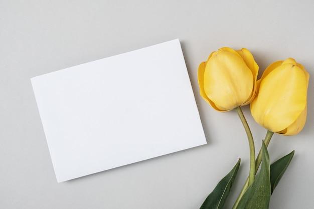 Tulipas amarelas e uma folha de papel branco copiam o espaço para o texto em um fundo cinza. um convite para uma festa ou aniversário ou um evento importante.