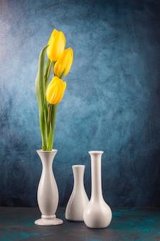 Tulipas amarelas e vasos vazios na mesa