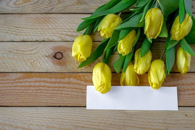 Tulipas amarelas em fundo de madeira. pode ser usado como plano de fundo