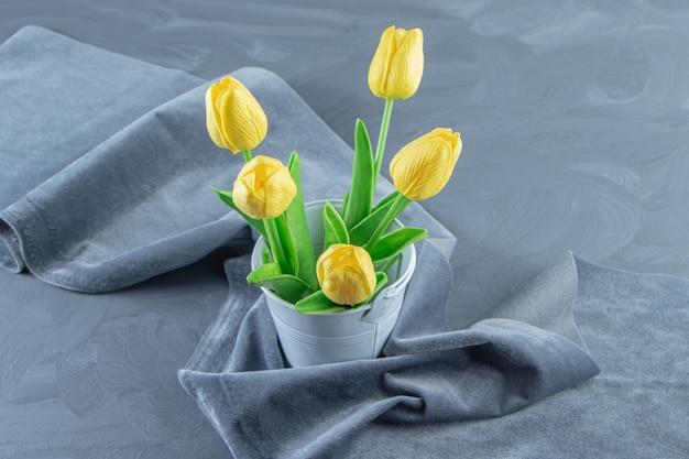 Tulipas amarelas em um balde em um pedaço de tecido, sobre fundo branco.