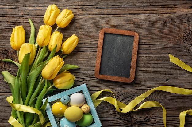 Tulipas amarelas em um saco de papel, um ninho com ovos de páscoa em um fundo de madeira. vista superior com espaço de cópia