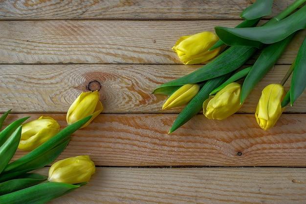 Tulipas amarelas em uma mesa de madeira. pode ser usado como plano de fundo