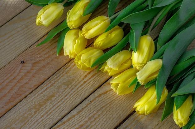 Tulipas amarelas frescas em fundo de madeira. pode ser usado como plano de fundo