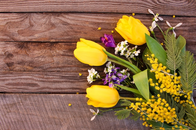Tulipas amarelas, mimosa na madeira velha