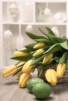 Tulipas amarelas, ovos de páscoa e decorações em um shadowcase