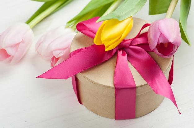 Tulipas amarelas rosa vermelhas e caixa de presente com fita vermelha