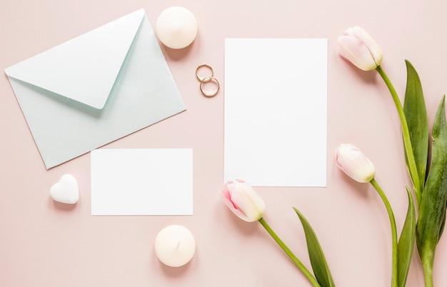 Tulipas ao lado de anéis de noivado e cartão de convite