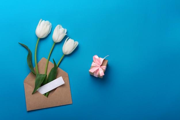 Tulipas brancas com caixa de presente, uma nota de amor e envelope em um fundo azul