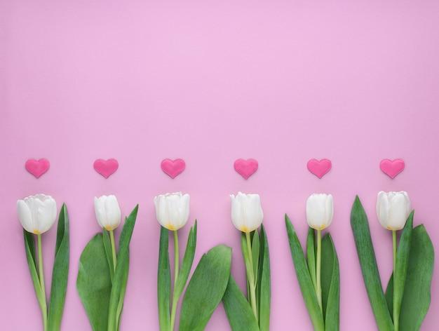 Tulipas brancas com corações no fundo rosa. hapy dia dos namorados.