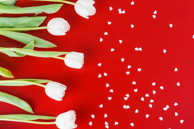 Tulipas brancas com pequenos corações na mesa