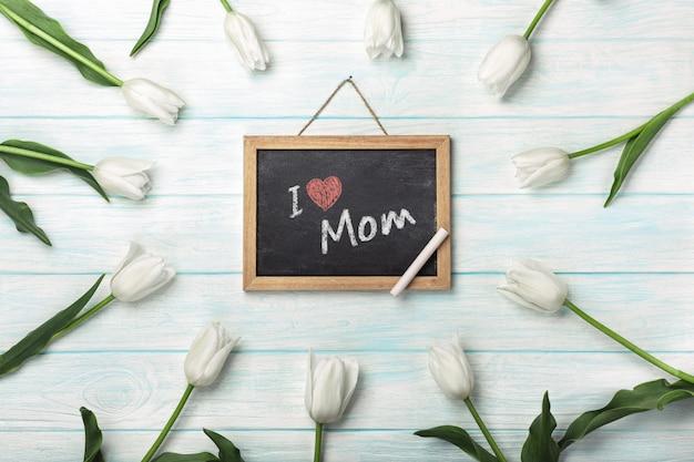 Tulipas brancas com placa de giz em placas de madeira azuis. dia das mães