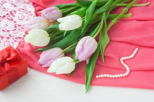 Tulipas brancas e roxas e um presente em uma caixa vermelha sobre um fundo branco de madeira