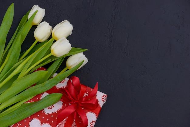 Tulipas brancas e um presente vermelho com impressão de coração e espaço de cópia para saudações