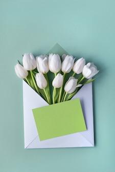 Tulipas brancas em envelope de papel com adesivo decorativo coração em fundo de papel verde menta claro