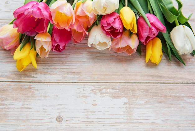 Tulipas coloridas da primavera em uma superfície de madeira