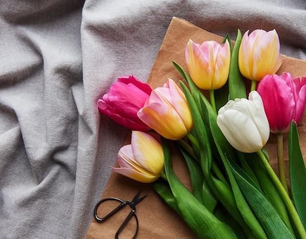 Tulipas coloridas da primavera em uma superfície têxtil