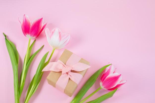 Tulipas coloridas e caixa de presente na superfície rosa