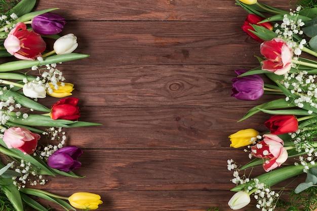 Tulipas coloridas e flor de respiração do bebê no lado da superfície texturizada de madeira