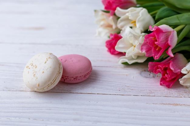 Tulipas com biscoitos em fundo branco de madeira. tulipas rústicas.
