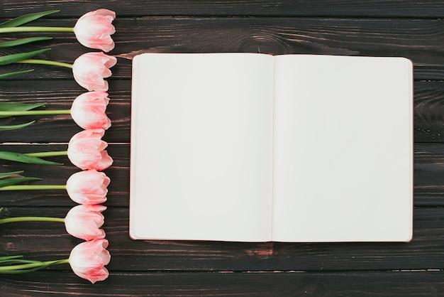Tulipas com caderno em branco na mesa
