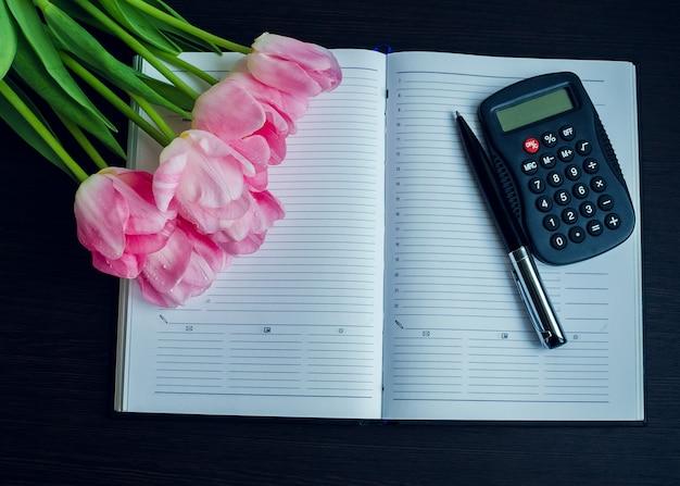 Tulipas com caneta e calculadora no caderno vazio