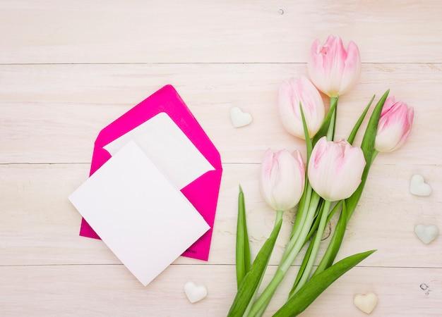 Tulipas com papel em branco e envelope