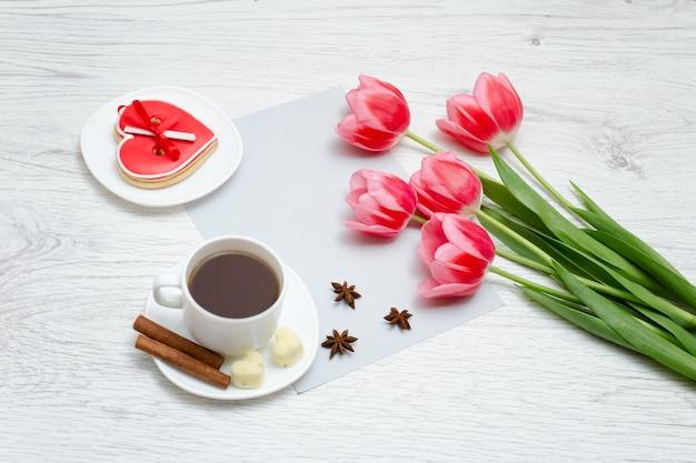Tulipas cor de rosa, caneca de café e pão de gengibre vermelho.