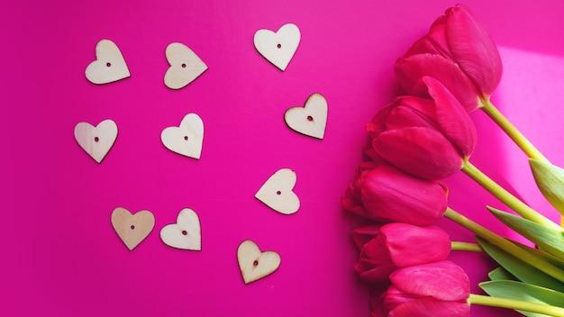 Tulipas cor de rosa com corações no fundo rosa. camada plana, vista superior. plano de fundo dia dos namorados. conceito de primavera.