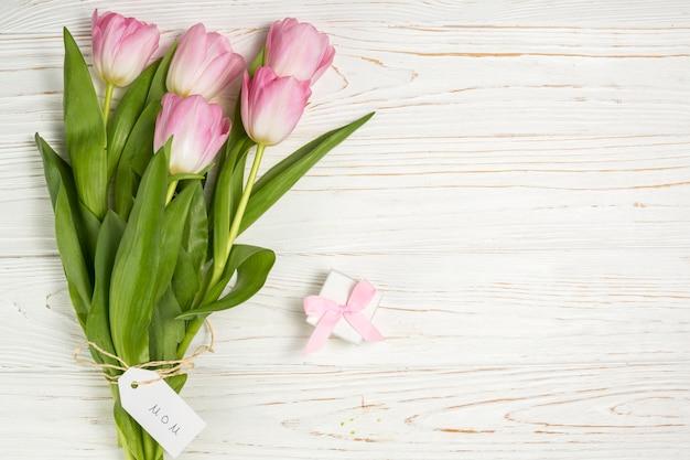 Tulipas cor de rosa com pequeno presente e inscrição de mãe