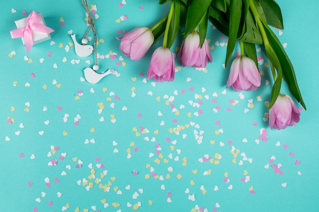 Tulipas cor de rosa com pequenos pássaros e caixa de presente