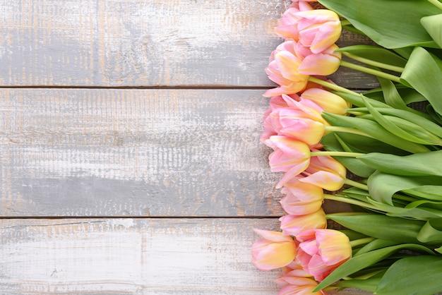Tulipas cor de rosa com tonalidade amarela em fundo de madeira rural cinza e branco com espaço de cópia