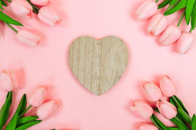 Tulipas cor de rosa da primavera e um dia dos namorados de madeira em forma de coração, em um fundo rosa