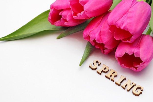 Tulipas cor de rosa e a palavra primavera