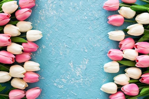Tulipas cor de rosa e brancas sobre fundo azul grunge