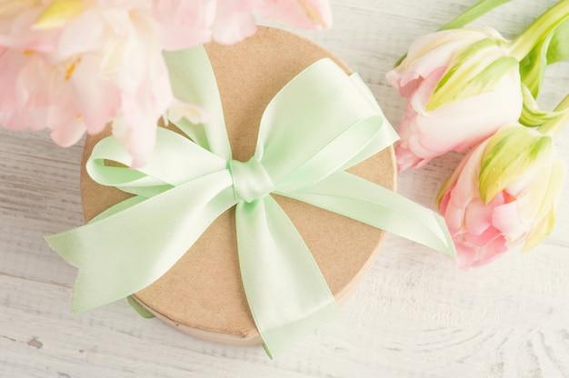 Tulipas cor de rosa e caixa de presente com fita verde